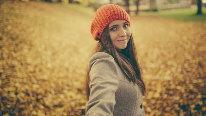 Young woman pulling her boyfriend through autumn park with leafs pov - HD stock footage clip