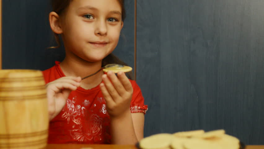 Girl puts honey on the spoon cookies - HD stock footage clip