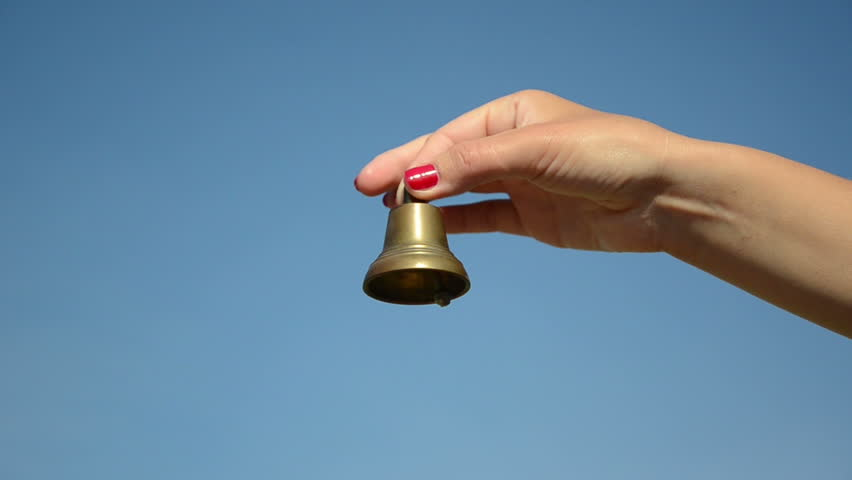 hand with red nails shake small iron bell and jingle sound on background of blue sky. - HD stock video clip