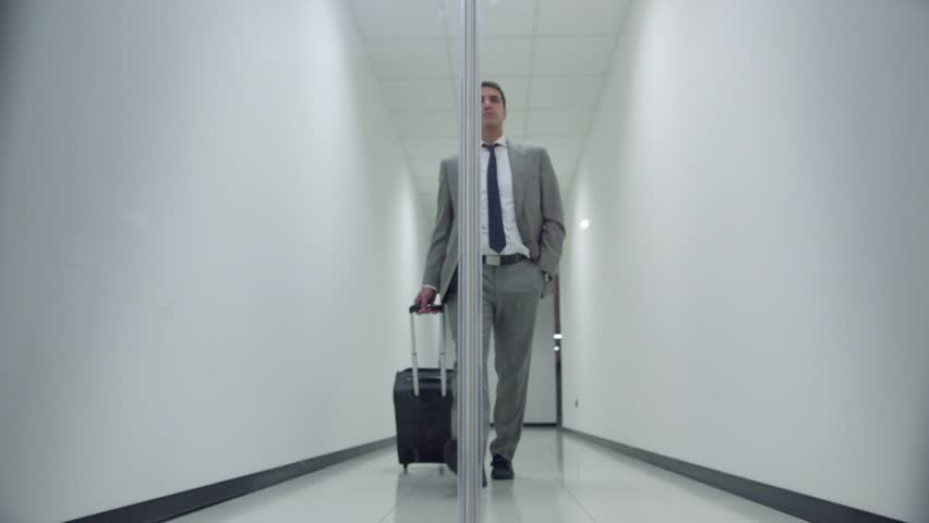 Business man walking with trolley in corridor of office building and passing through automatic door. Sequence, 1of20