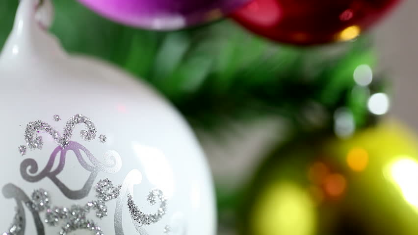 Dolly shot of coloured Christmas balls on tree.