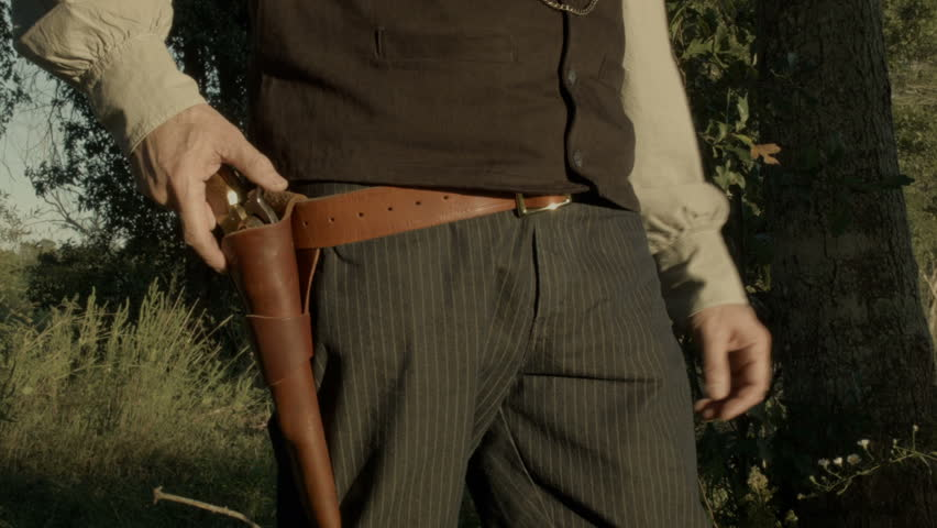 A cowboy from the American wild west era fires his black powder pistol