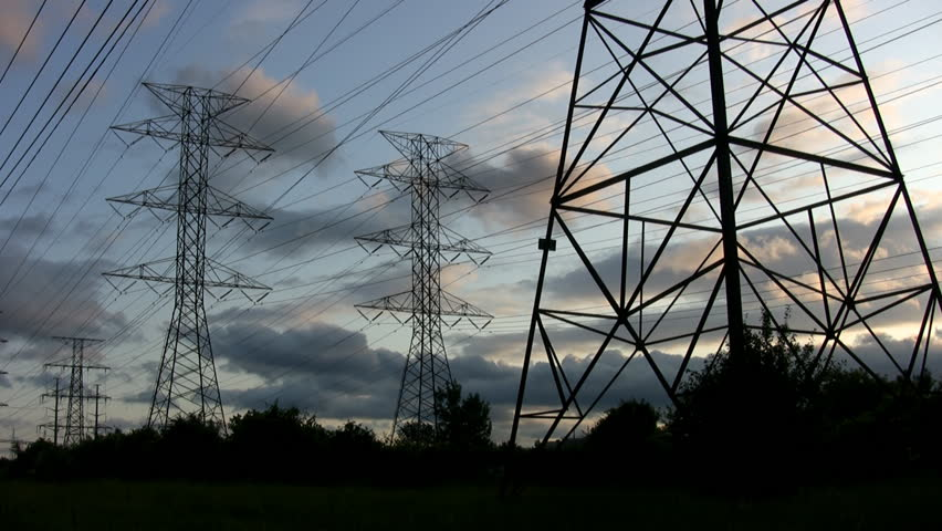 Electric pylons at sunset with timelapse clouds passing by. - HD stock video clip