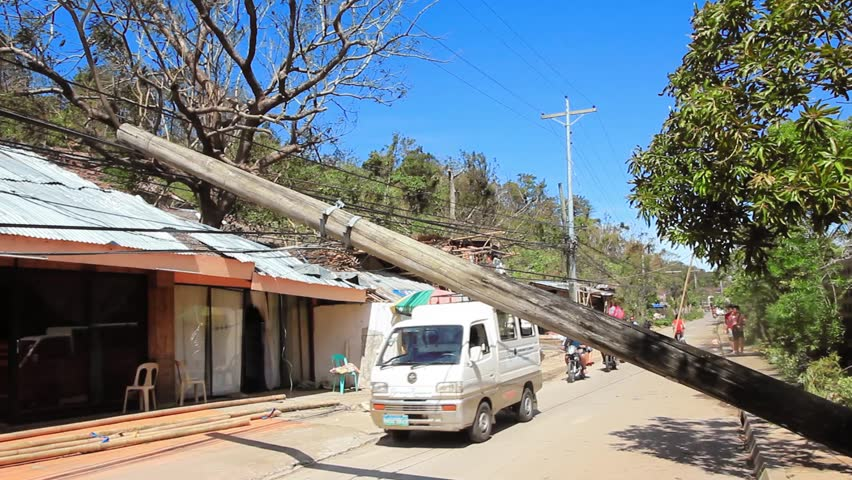 Boracay, Philippines - November 9 2013:  Super Typhoon Haiyan causes wide spread disruption to utility and power infrastructure and people drive under fallen power poles