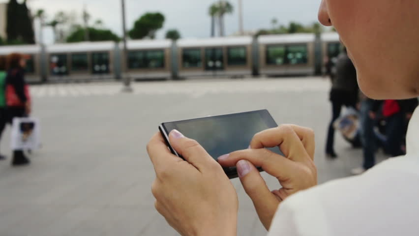 Close up of a woman using mobile smart phone outdoor
