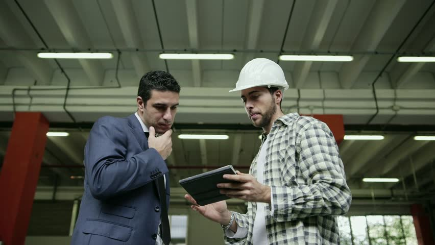 Manager in logistics facility talking to manual worker with digital tablet computer, people working in warehouse, workers in industry. 2of19