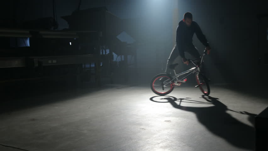 BMX rider doing tricks in dark warehouse - HD stock video clip