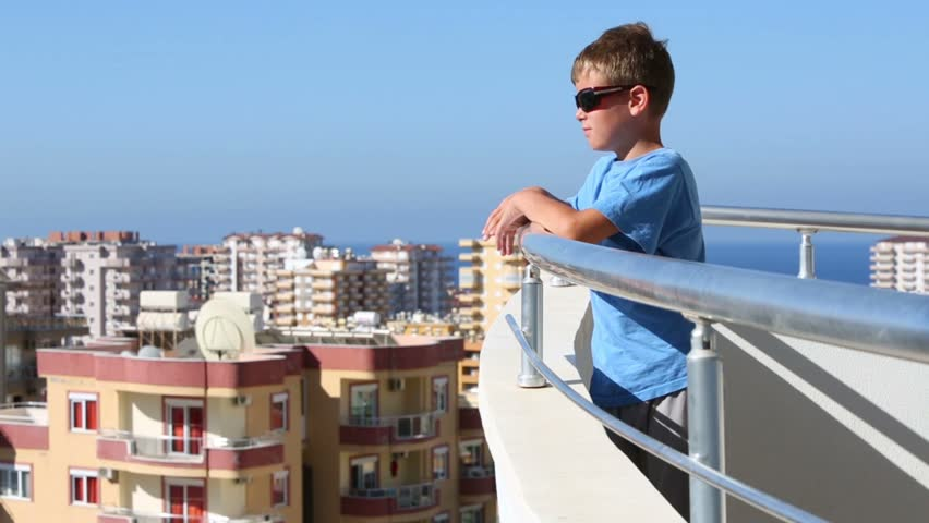 Little boy in blue shirt standing on a balcony overlooking for Balcony overlooking city