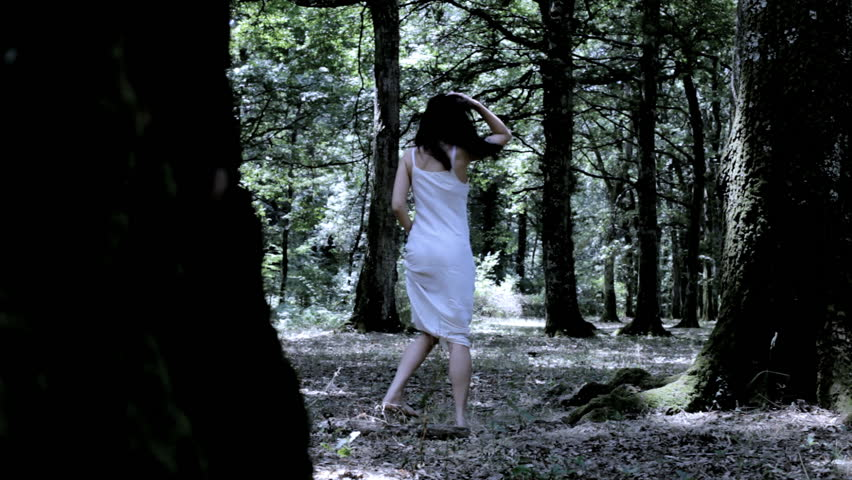 Scared female model running in forest looking for help