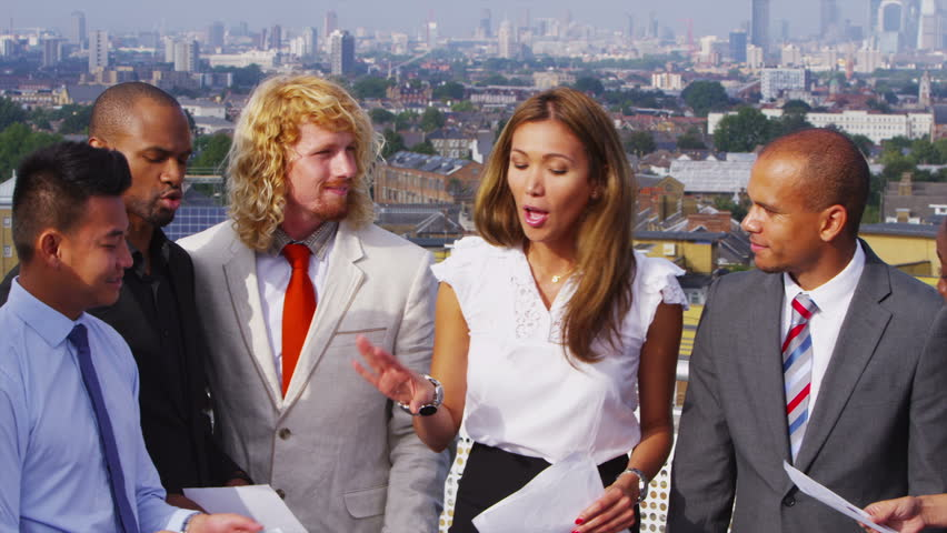 Attractive mixed ethnicity business team in open air meeting on rooftop terrace with views of the city in the background behind them. In slow motion.