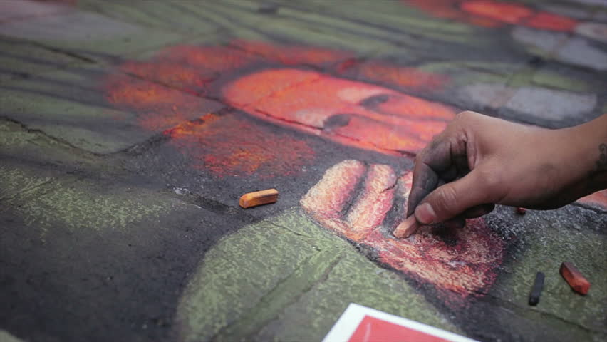 GUANAJUATO, MEXICO -CIRCA NOVEMBER 2013: Artist finishes painting over the asphalt in Madonnari festival of chalk paintings