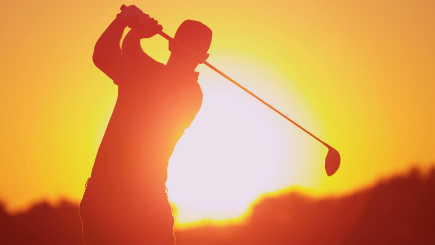 Silhouette weekend male golfer enjoying time golf course in summer driving off down fairway sunset shot on RED EPIC, 4K, UHD, Ultra HD resolution