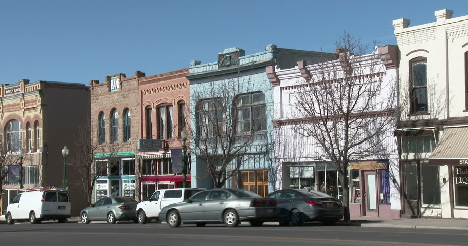 MNT PLEASANT, UTAH JAN 2013: Rural town economic business center old stores traffic 4K. Farming community with very small business section. Main Street. Vehicles pass downtown. Colorful architecture.
