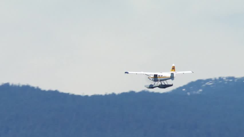 Sea plane flying over mountains in Vancouver, British Columbia. - HD stock video clip