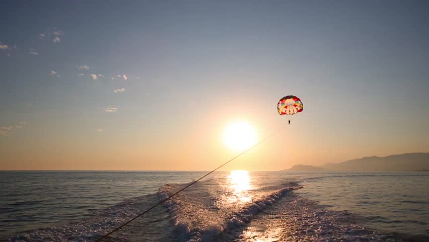 Glider flies over sea at sunny summer evening and traces of boat on water - HD stock footage clip