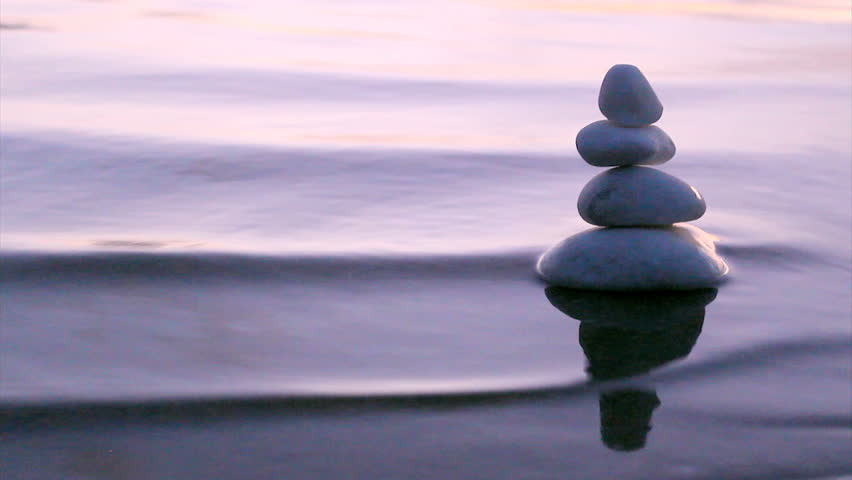 Stack of round smooth marble stones in Zen style and sea waves background - HD stock video clip