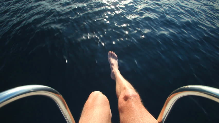 pov feet on a moving boat at railing