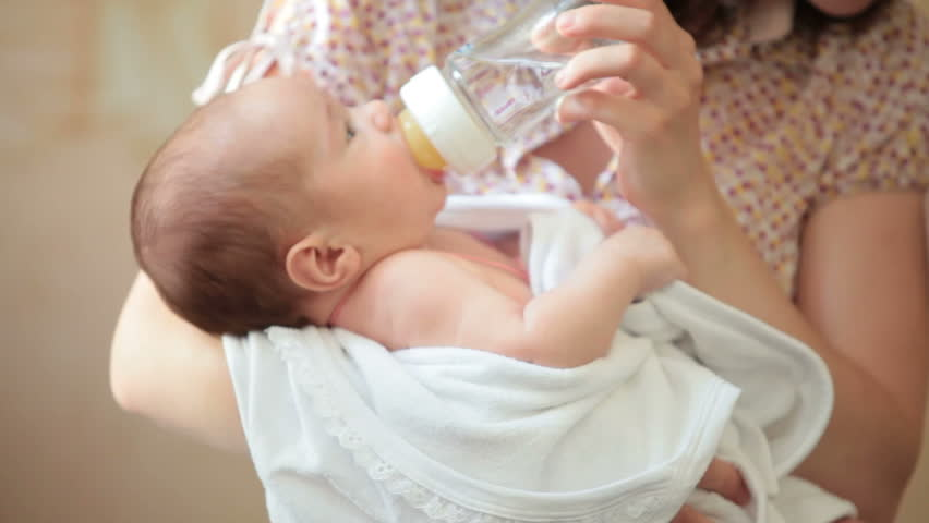 Mother feeding baby girl from the baby bottle