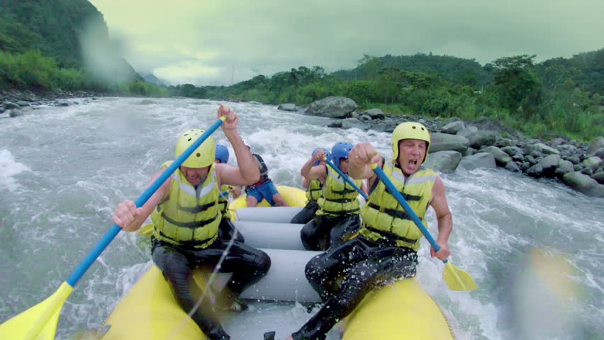 Team of six people white water rafting. On board camera.
