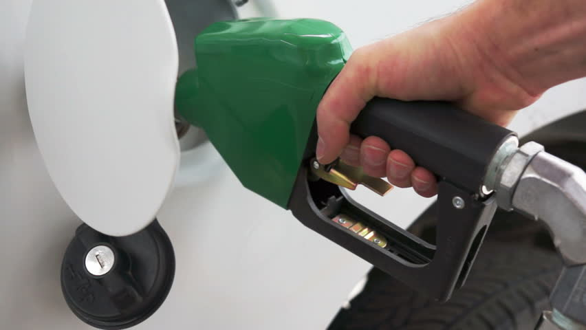 Close up shot of insertion of the nozzle and pumping gasoline into a white vehicle at the gas station.