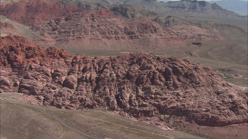 Las Vegas Desert Mountains. Aerial footage of the mountains and the desert surrounding Las Vegas. Steep red cliffs are raised over the desert.
