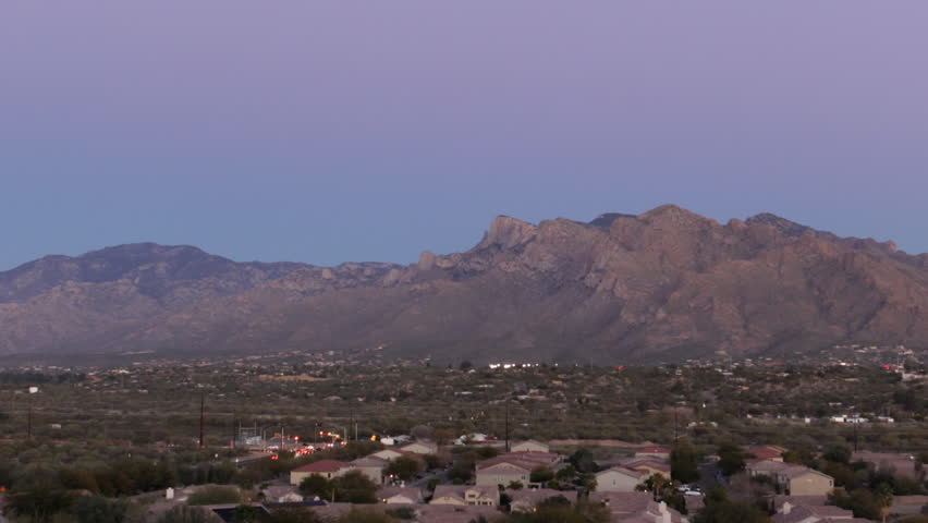 Timelapse of the Santa Catalina mountains in Tucson, Arizona glowing violet and blue at dusk, with the full moon rising over the hills in silhouette as darkness falls. Seen from Oro Valley.