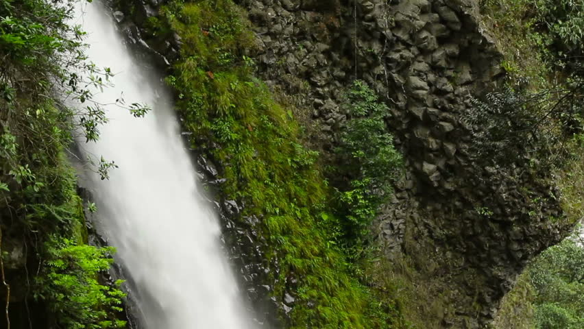 Pailon del Diablo waterfall in Ecuadorian Andes, camera tilts and pan following the water course. - HD stock footage clip