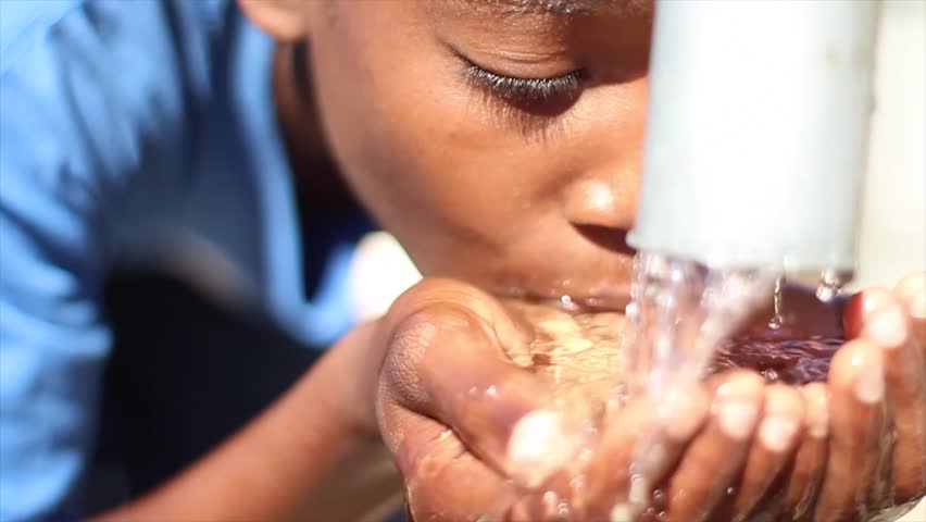 PORT AU PRINCE, HAITI - DECEMBER 17, 2013: Unidentified boy drinking water at well in Port au Prince, Haiti.