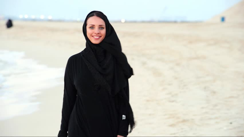 Middle eastern woman. pretty lady walks at sunset alone sea coast.