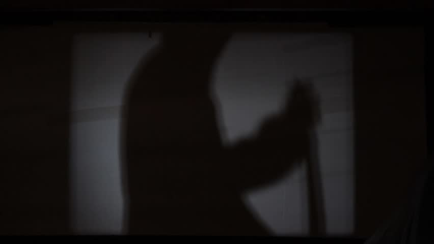 Killer silhouette, killing and stab victim with a knife. Abstract horror scene of psycho serial killer who stab with big knife, shadow on the old cinema screen. Murderer stabbing with knife. Close up.