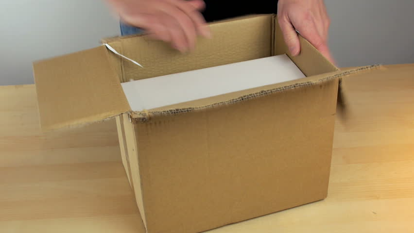 A parcel delivery, cardboard box opened and a small white box taken out in the office.
