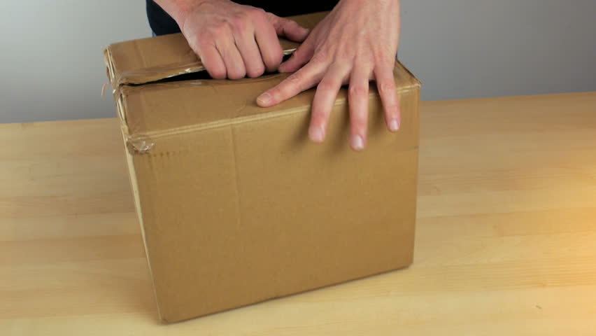 An office worker opening a boxed delivery and taking out a white boxed package.
