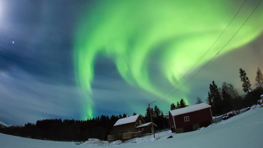Northern lights dancing on a typical house in Norway.