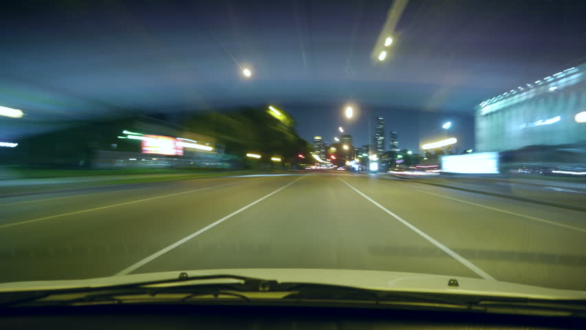 4k - Driving a car time-lapse. POV - point of view. Night, Camera in the front, windshield reference. City, blurred motion, fast driving. - 4K stock video clip