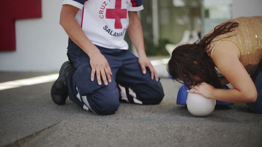 GUANAJUATO, MEXICO CIRCA FEBRUARY 2014: Staged scene: Student learning CPR meanwhile paramedics go out red cross facilities for an emergency call during training session for new volunteers