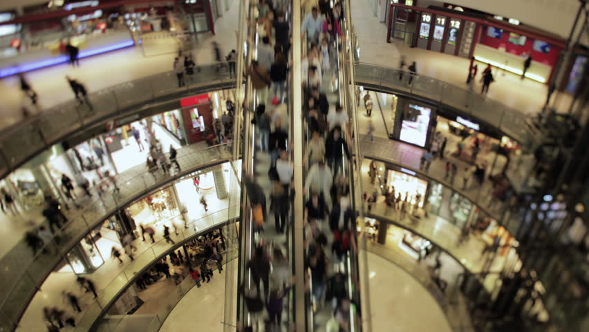 Shift and tilt wide angle time lapse of an escalator and people passing in a big round square at a mall. 4K