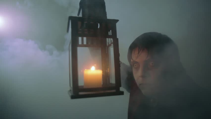 A vampire with a lamp in his hands in the mist of the night (scary man dressed in Halloween costume)