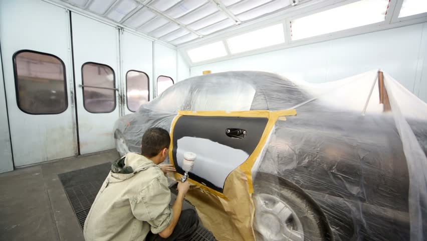 Man paints car door with automotive primer at painting booth - HD stock video clip