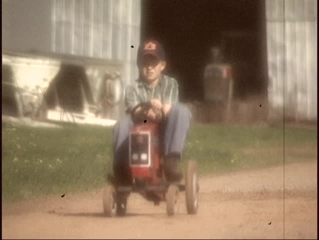 Slow motion - Vintage film look of a Rural farm boy (approximately 8 yrs. old) with a tractor pedal toy heading to the barn. - SD stock video clip
