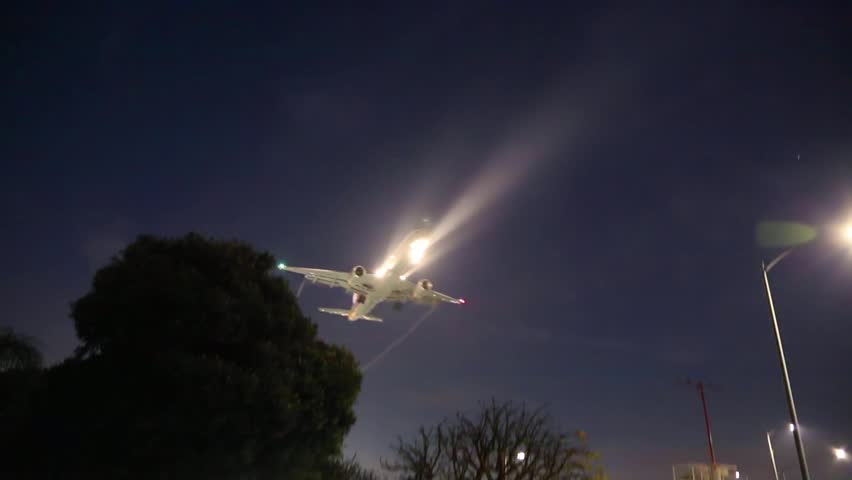 Jet airplane approaching landing at night in Los Angeles LAX airport.