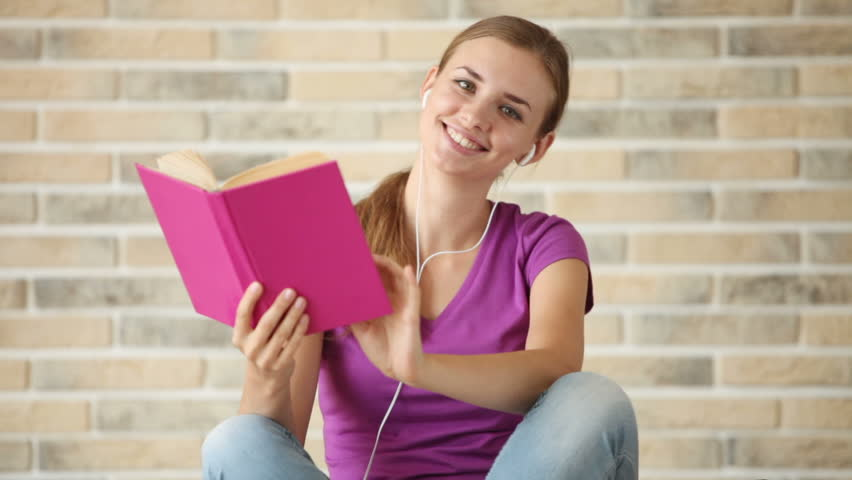 Beautiful girl wearing earphones sitting on floor reading book looking at camera and smiling. Panning camera