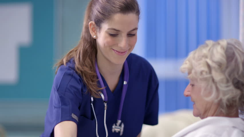Caring nurse chats with a female patient on a hospital ward. - HD stock footage clip