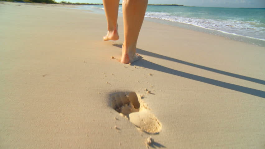 Young caucasian girl leaving footprints in the white sand of a tropical beach 60 FPS