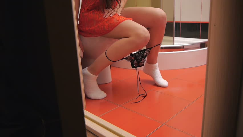 Girl sitting on the toilet in the bathroom