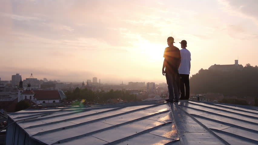 AERIAL: Two young skateboarders standing on rooftop