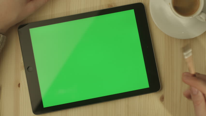 Man using Tablet in Coffee Shop. Tablet with Green Screen. Shot on RED Digital Cinema Camera in 4K (ultra-high definition (UHD)), so you can easily crop, rotate and zoom, without losing quality.