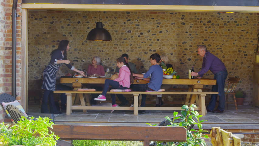 Happy extended family group enjoying a meal together in countryside home stock footage video - Countryside homes parents welcoming ...