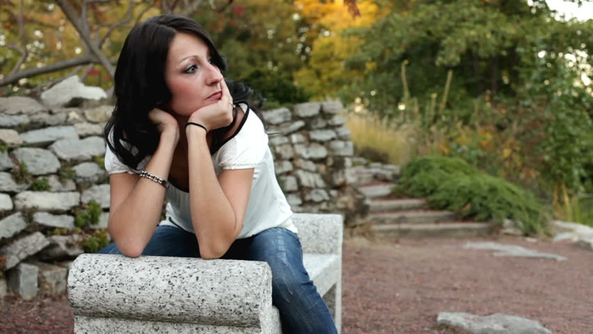 Girl with head in hand leaning on park bench - HD stock video clip