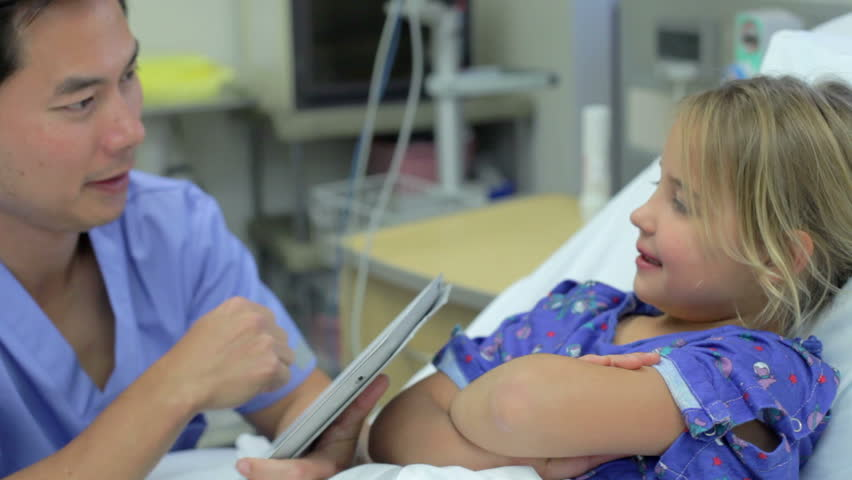 Camera moves around bed as male nurse with digital tablet talks to young female patient. - HD stock footage clip