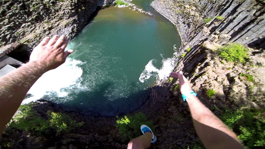 Extremely High POV Cliff Jump into Water above a Waterfall Trees and Rocks Below on a Beautiful Sunny Day in Summer in the Forest with a Thumbs Up to Bystanders Extreme Fun Point of View Head Camera